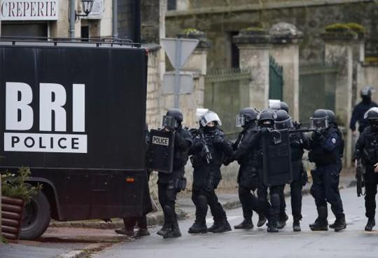 Cảnh sát tìm kiếm từng ngôi nhà trong làng Longpont, Đông Bắc Paris, hôm 8-1. Ảnh: Reuters