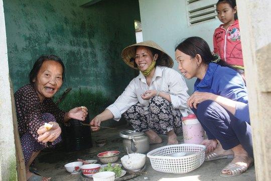 Bà Phạm Thị Sòng (bìa trái) dùng bữa cơm trưa do nhà bà Bùi Thị Thu Tuyết nấu dọn