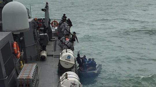 Nhặt nhạnh các vật dụng trên chuyến bay QZ8501 từ biển cả hôm 4-1. Ảnh: Reuters