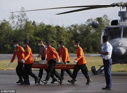 Một thi thể được đưa về đất liền trong ngày 2-1. Ảnh: Reuters