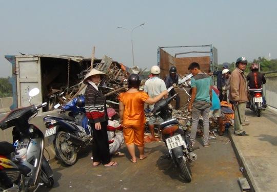 Phế liệu trên chiếc xe tràn xuống đường, chắn ngang làn xe máy trên cầu Phú Mỹ