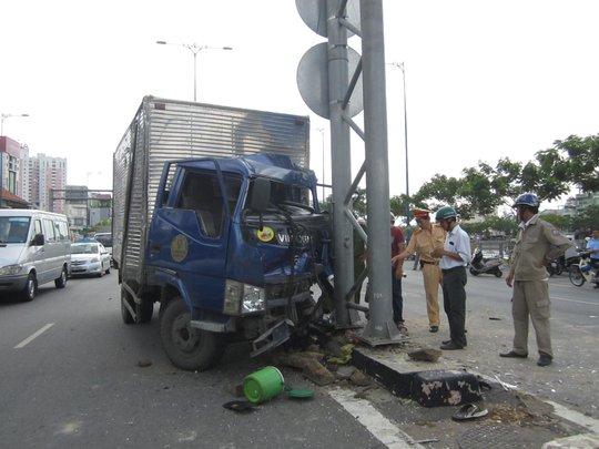 Chiếc xe tải bẹp dúm phần đầu sau cú tông xe máy rồi lao vào trụ đèn giao thông