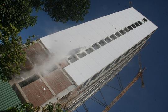 Cát bụi từ khách sạn Mường Thanh được các công nhân đổ từ trên cao xuống