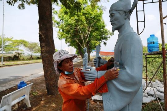 Nghệ nhân đang đo đạc bức tượng bằng chất liệu nhựa để tạc lại bằng đá hoa cương