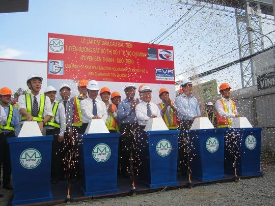 Thứ trưởng Bộ GTVT Nguyễn Ngọc Đông cùng lãnh đạo UBND TP HCM và tỉnh Bình Dương thực hiện nghi thức lắp đặt đốt dầm đầu tiên của tuyến metro số 1 sáng 4-6