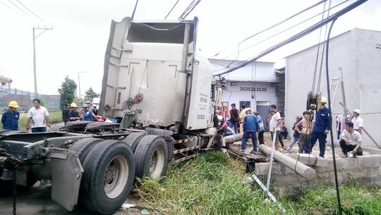 Chiếc xe container mất lái tông gãy trụ điện và ủi sập tường nhà dân, vào rạng sáng 21-7