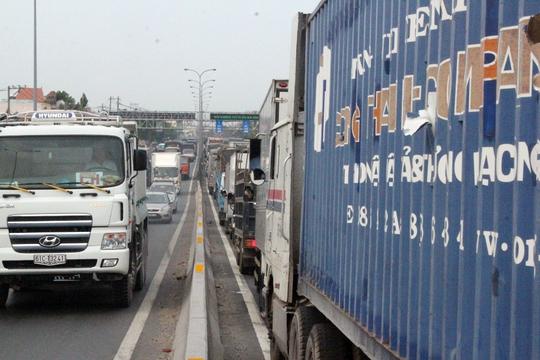 Các phương tiện xe ô tô phải xếp thành hàng dài trên Quốc lộ, nhiều tài xế xe tải nóng ruột vì kẹt xe quá lâu xuống đường ngóng nhìn