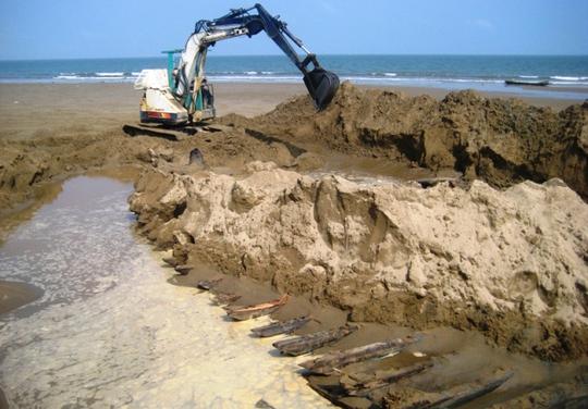 Xác con tàu gỗ vùi trong cát đang được cơ quan chức năng khai quật