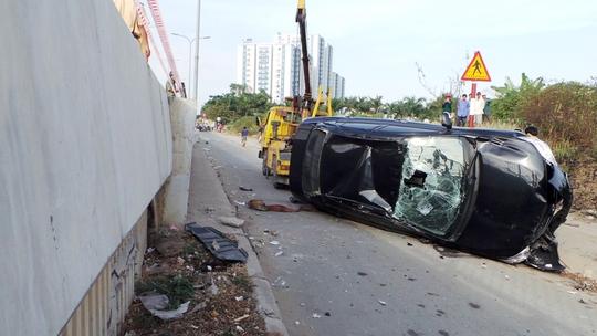 """Do gặp phải """"bẫy"""" bùn thải tại cầu Rạch Cây trên đại lộ Võ Văn Kiệt (quận 6) chiếc ô tô biển xanh mất lái bay từ cầu xuống đường."""