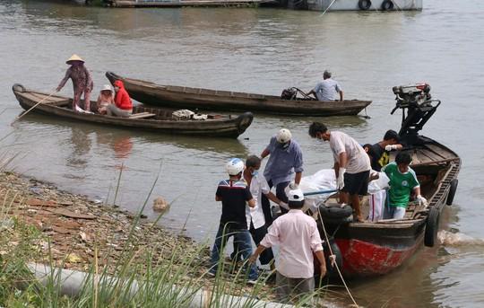 Ảnh các lực lượng chức năng đưa thi thể vợ con chủ ghe chở đá lên bờ để đưa về quê an táng.