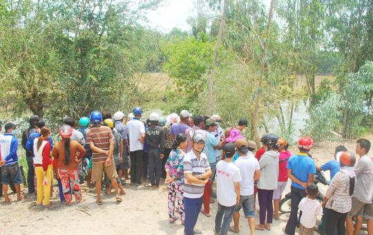 Người dân hiếu kỳ đến xem thi thể của nạn nhân khi còn nằm dưới mé kênh.