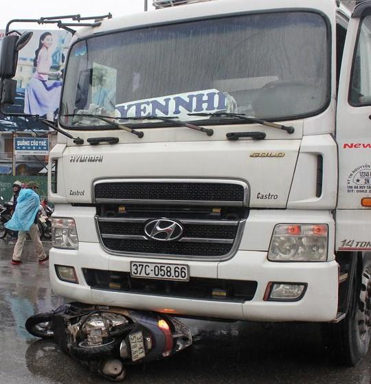 Xe máy của 2 cố gái bị xe tải cuốn vào gầm.