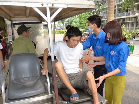 Sinh viên tình nguyện tham gia hướng dẫn, giúp đỡ bệnh nhân nhằm giảm thời gian chờ đợi khi đến BV Bạch Mai khám chữa bệnh sáng 4-7 Ảnh: NGỌC DUNG