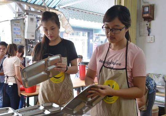 Các tình nguyện viên lau khay đựng cơm trước khi phục vụ cho người nghèo ở quán Nụ cười Đà Nẵng