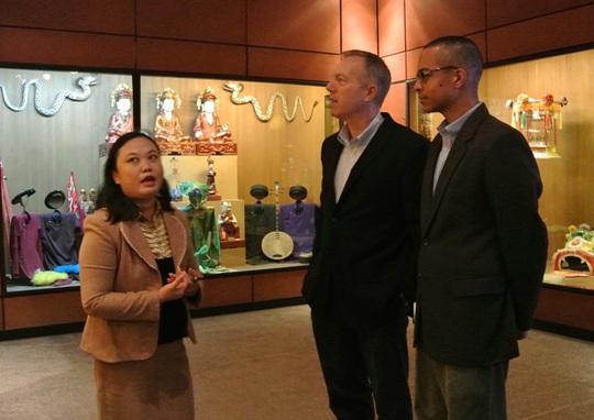 Hai ông nghe hướng dẫn viên bảo tàng giới thiệu về văn hoá truyền thống Việt Nam