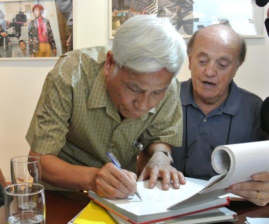 """ông Peter Arnett đã kiên quyết """"đòi"""" mua quyển sách ảnh ghi lại hoạt động của thanh niên Việt Nam trên tuyến đường Hồ Chí Minh chi viện cho miền Nam trong kháng chiến chống Mỹ mà không nhận nó như một món quà tặng. Ảnh: Nhà báo Văn Sắc của Thông tấn xã Việt Nam viết lưu niệm lên cuốn sách"""