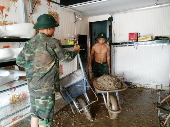 Bộ đội giúp người dân dọn nhà sau trận lụt