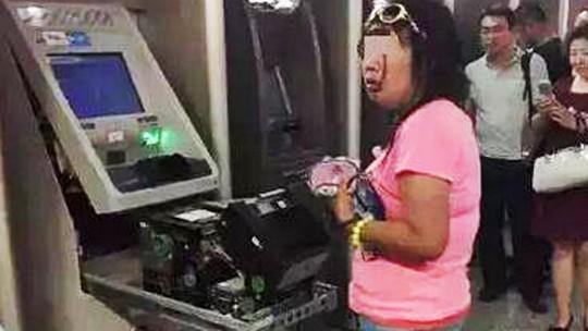 Người phụ nữ tay không tháo tung máy ATM. Ảnh: SCM