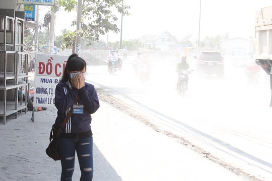 Một sinh viên chờ xe buýt bịt mũi khi dừng ở đoạn đường này
