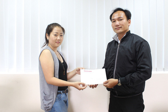 Đại diện Báo Người Lao Động (trái) trao tiền cho anh Phan Văn Nam (anh của chị Thơm)