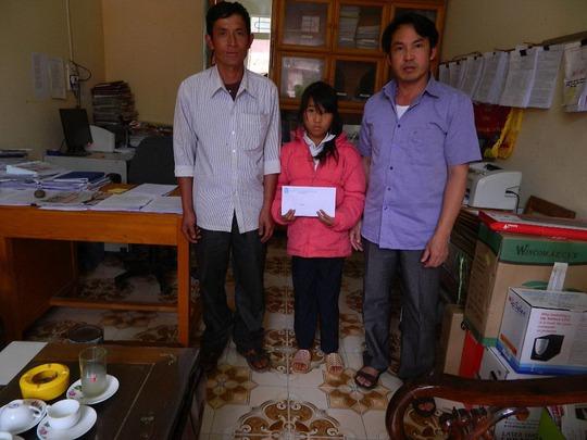 Ông Nguyễn Đức Mạnh, Chủ tịch LĐLĐ huyện Mù Cang Chải, trao tiền của bạn đọc đến em Hảng Thị Dùa