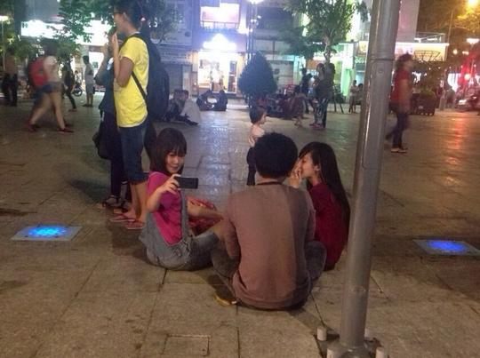 Nhiều nhóm bạn trẻ vô tư bày đồ ăn, thức uống chắn giữa đường đi ở phố đi bộ Nguyễn Huệ