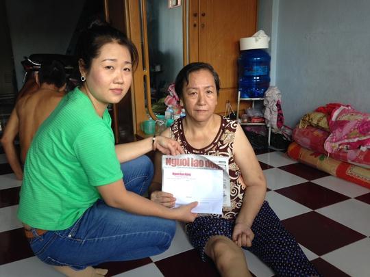 Đại diện Báo Người Lao Động trao tiền của bạn đọc giúp đỡ cho bà Trần Thị Huỳnh Hoa