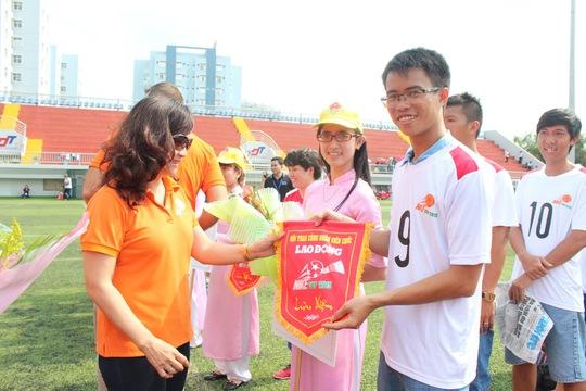 Cầu thủ Nguyễn Sỹ Đông của đội bóng đá Báo Người Lao Động nhận cờ lưu niệm của ban tổ chức