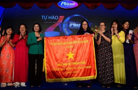 Lãnh đạo Thành ủy (trái) trao cờ truyền thống của UBND TP cho Tổng biên tập Báo Phụ Nữ TP HCM