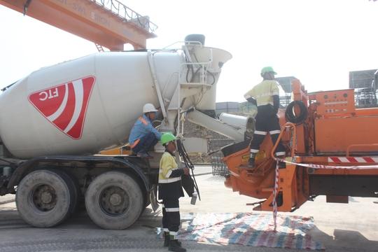 Các công nhân vận hành máy trộn bê tông để chuẩn bị cho việc đúc các dầm