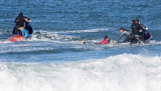 Fanning (áo xanh) và Julian Wilson (áo đỏ) được lực lượng cứu hộ đưa lên mô tô nước. Cả 2 đều bị cá mập tấn công khi đang lướt ván.