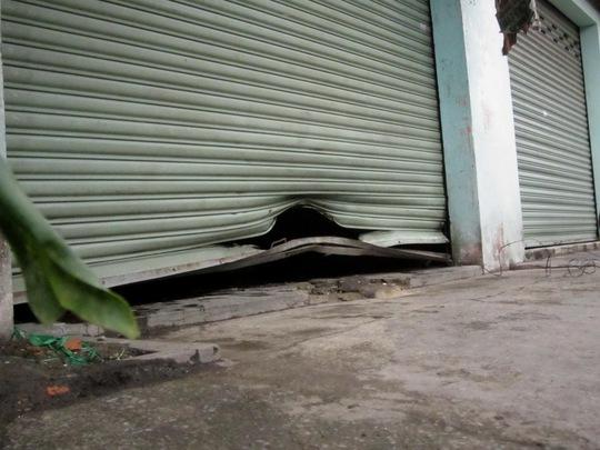 Cửa cuốn của căn nhà bị xé toạc, bẻ cong; nền nhà vỡ bung, lõm gần 10 cm sau vụ nổ