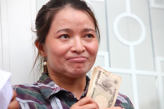 Chị Hồng xúc động nghẹn ngào cầm lại tiền trên tay