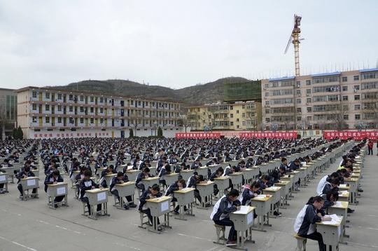 Học sinh làm bài dưới sân trường. Ảnh: SCMP