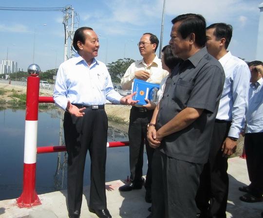 Bí thư Thành Ủy TP HCM Lê Thanh Hải (bìa trái) cùng nhiều lãnh đạo TP khảo sát công trình chống ngập trong buổi lễ bàn giao sáng 23-4 tại quận 8