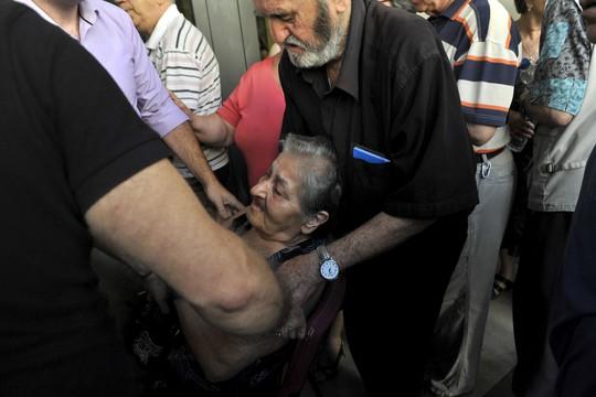 Cụ bà gục ngã khi đang xếp hàng đợi nhận lương hưu tại chi nhánh của Ngân hàng Eurobank ở TP Thessaloniki - Hy Lạp hôm 6-7 Ảnh: REUTERS