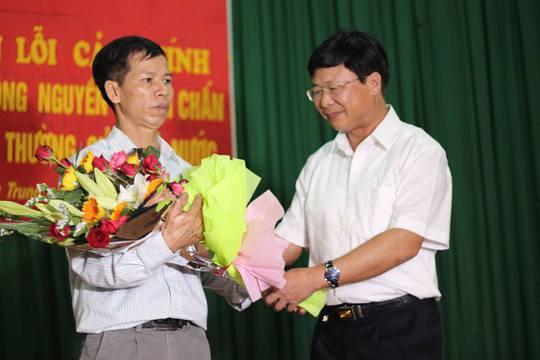 Ông Ngô Hồng Phúc, Phó Chánh Tòa Phúc thẩm TAND Tối cao tại Hà Nội (bên phải), xin lỗi và tặng hoa ông Nguyễn Thanh Chấn