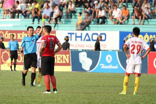 Văn Nam (phải) nhận thẻ vàng từ tay trọng tài Nguyễn Đức Vũ