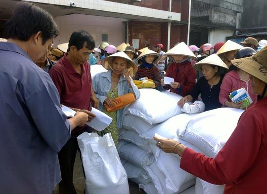 Dân nghèo nhận gạo cứu trợ đỏ lửa. Ảnh: A.Tú