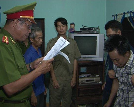 Bị can Trần Xuân Vinh (bìa phải, mặc áo ca rô) bị cơ quan CSĐT đọc lệnh bắt giam ngày tại nhà mình Ảnh do công an cung cấp