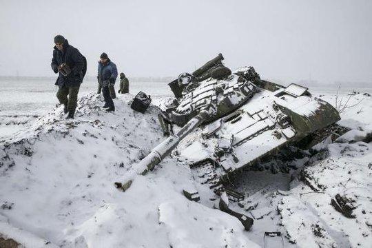 Những binh sĩ phe ly khai Donetsk thu thập một phần chiếc xe tăng bị phá hủy của quân đội Ukraine ở thị trấn Vuhlehirsk, Debaltseve 6 km về phía Tây. Ảnh: Reuters