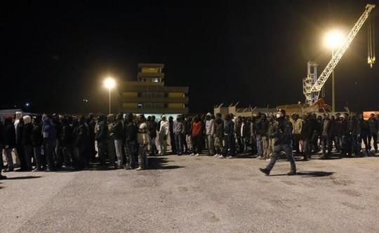 Cảnh sát hộ tống người di cư khi họ được đưa lên bờ từ một tàu hải quân tại cảng Sicily - Ý vào tháng 3. Ảnh: Reuters