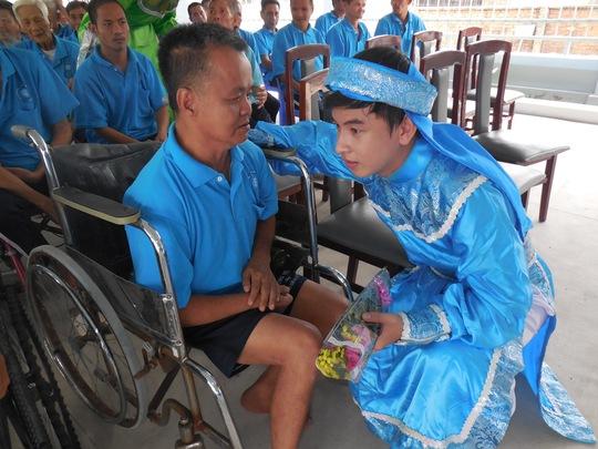 Diễn viên Huỳnh Quý thăm hỏi một bệnh nhân khuyết tật tại Trung tâm Thạnh Lộc