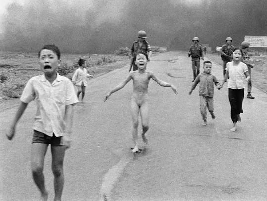 Bị bỏng nặng trong cuộc tấn công bằng bom Napalm, trẻ em chạy gào thét kêu cứu dọc đường 1 gần Trảng Bàng, phía sau là lính của Sư đoàn 25 của Việt Nam Cộng hòa ngày 8-6-1972. Cô bé Kim Phúc, 9 tuổi, (ở giữa) đã cởi quần áo bị cháy trong khi chạy. Những trẻ em khác (từ trái) là anh của cô Phan Thanh Tâm, người bị mất một mắt và Phan Thanh Phước và anh em họ Hồ Văn Bốn và Hồ Thị Tung. Bức ảnh này của Nick Ut đã giành được giải Pulitzer cho ảnh thời sự năm 1973.