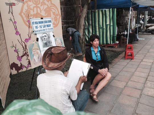 Một du khách nước ngoài thích thú với việc vẽ ký họa chân dung trong Hội chữ Xuân Ất Mùi.