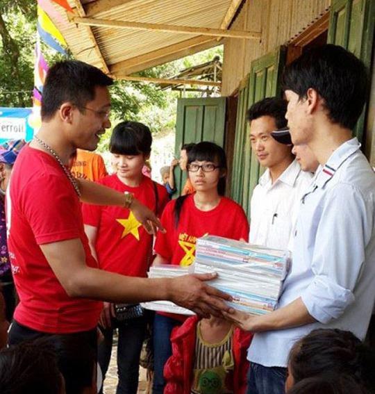 Nhóm trưởng Nguyễn Vũ Thăng (bìa trái) trao sách, vở cho học sinh ở điểm trường Ngài ThầuẢnh: Nguyễn Vũ