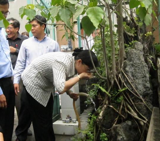 Bà Nguyễn Thị Quyết Tâm uống nước từ giếng khoan trong buổi giám sát tại phường Bình Chiểu, quận Thủ Đức và sáng 12-5