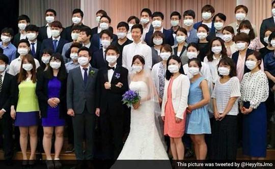 Bức ánh kỷ niệm cưới với những người tham dự đeo khẩu trang lan truyền trên mạng. Ảnh: Twitter
