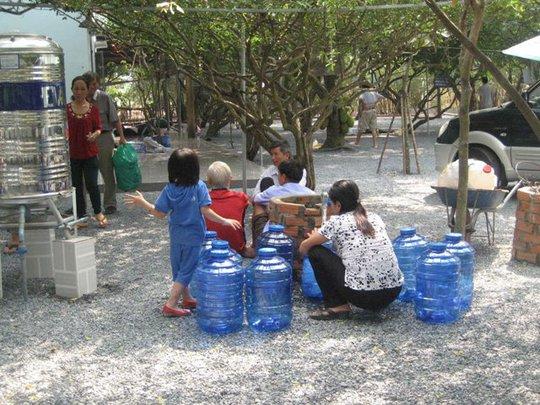 Hứng nước từ vòi nước máy để đem về uống chữa bệnh