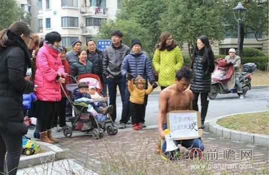 Anh Wang quỳ trước chung cư, nơi anh sống cùng vợ. Ảnh: Shanghaiist